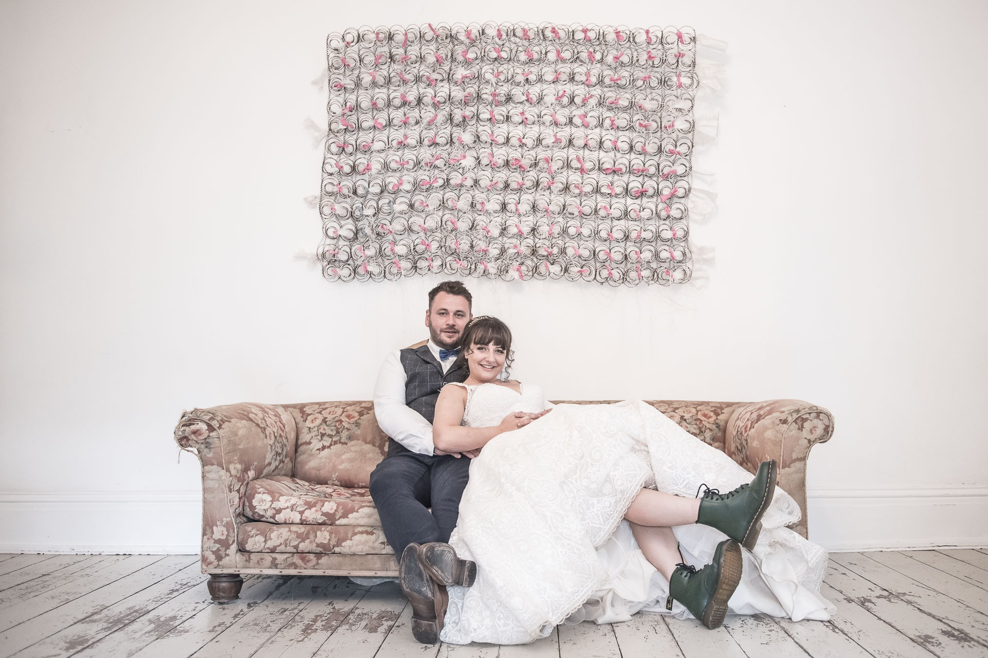 bride-and-groom-having-a-cwtch-on-a-sofa-during-their-wedding-day