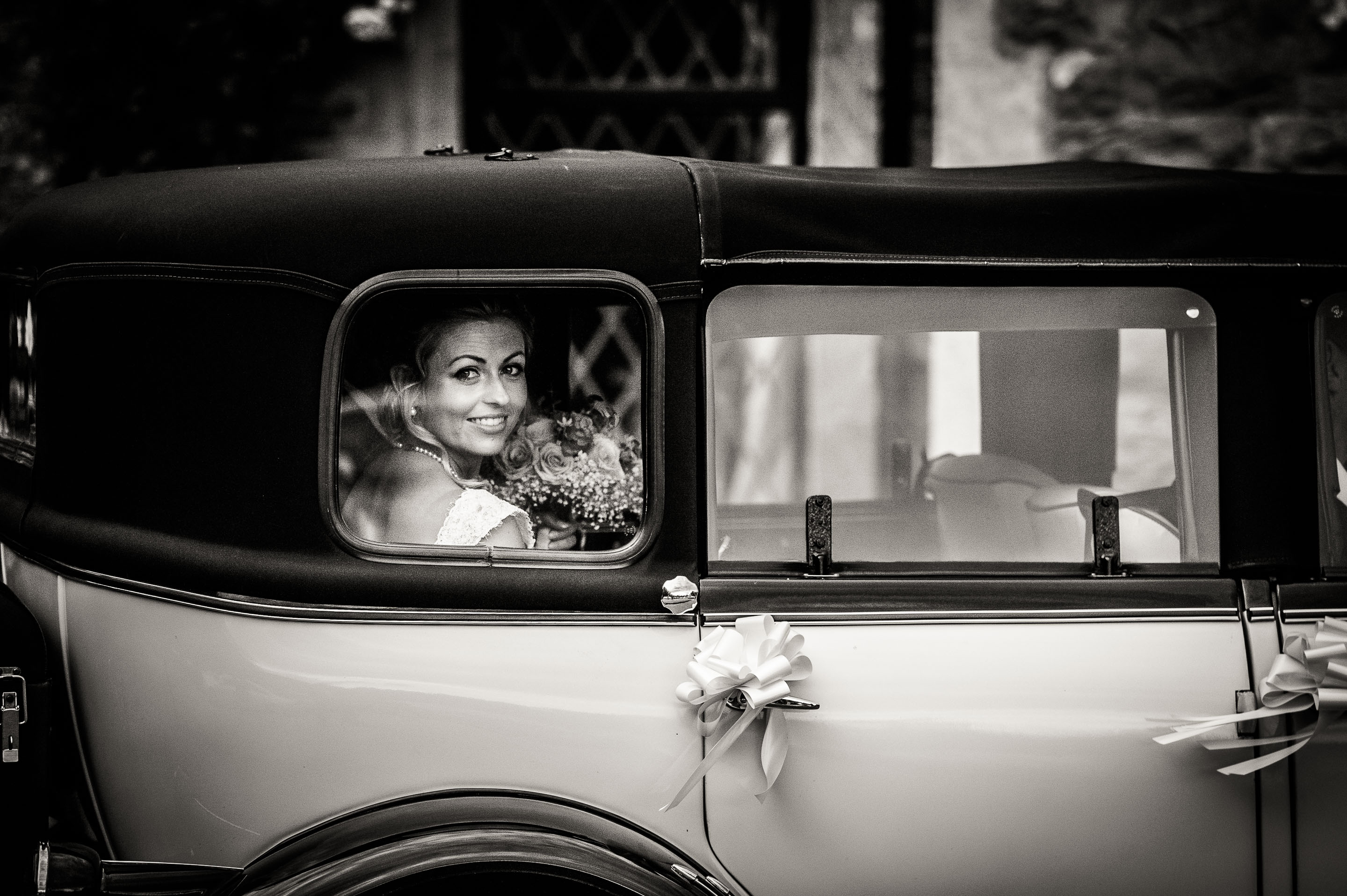 bride-smiles-in-the-back-of-the-wedding-car-as-she-arrives-at-miskin-manor
