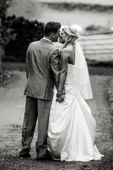 Bride and grom kissing on a path